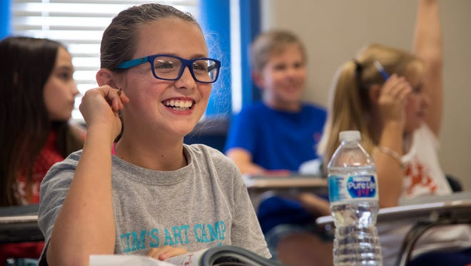 Fifth-grader Jenna Buck smiles Thursday, Oct. 26, 2017, as classmates take turns reading aloud in Jules Walkers' fifth grade reading and language arts class at Medina Middle School. Last year's standardized testing results saw Gibson County Special Schools District score among the highest in the state for grades three through eight. GCSSD was also the highest rated in rural West Tennessee for the 2016-17 school year.
