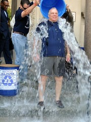 State Senate President Steve Sweeney gets doused with ice water to answer the ALS Ice Bucket Challenge on Monday on the front steps of the Statehouse in Trenton. At least he dressed for the occasion.