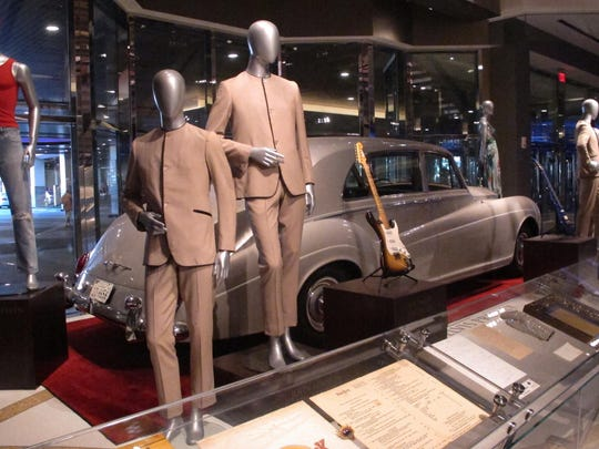 This photo shows suits worn by the Beatles during an early tour of America in front of the Rolls Royce automobile owned by Elvis Presley, part of a large collection of music memorabilia on display at the Hard Rock casino in Atlantic City.
