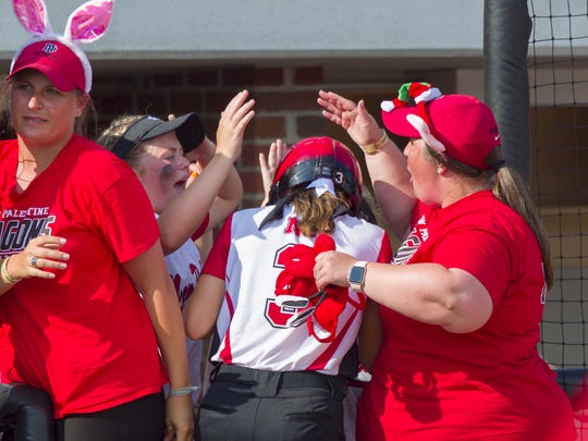 New Palestine High School junior Tete Hart (3) is greeted in the dugout by her teammates after scoring the team's first run during the 34th Annual IHSAA Softball State Finals class 3A game, Saturday, June 9, 2018, at Bittinger Stadium on the campus of Purdue University, West Lafayette. New Palestine High School won over South Bend St. Joseph High School 3-1.