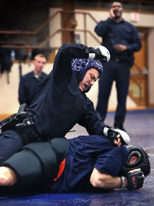 Brittany Waltz, one of 26 Indianapolis Metropolitan Police Department officer recruits, subdues an instructor playing a resistor during training.