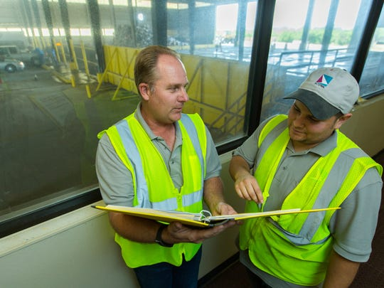 South Central Solid Waste Authority regulatory compliance specialist Steve Mauer, left, and transfer station attendant Arturo Ramos, right, discuss safety changes on Friday May, 13, 2016, that are being made at the facility after working with OSHA to ensure the workplace is safe.