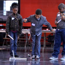 Khareah Walker, center, 11, launches a rocket as his sister, Kajhana Walker, left, 10, holds the launch pad still with her foot as Camron Hawkins, right, 10, all of Detroit, waits his turn.
