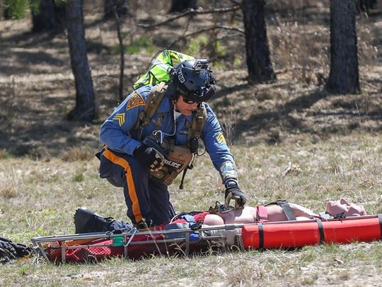 "NJ State Police Sgt. Christian Dreyer prepares a ""package"", a victim to be airlifted by State Police helicopter, during Operation Derecho, a full-scale search and rescue exercise hosted by the NJ State Office of Emergency Management at Fort Dix on April 17, 2016."