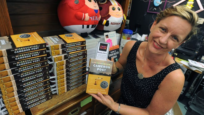 Browseabout Books store manager Susan McAnelly holds a copy of 'The Miseducation of Cameron Post,' a novel recently scratched from the freshman summer reading list by Cape Henlopen schools.