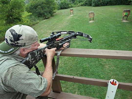 A crossbow is sighted-in from an elevated stand.
