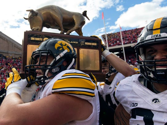 The Iowa Hawkeyes celebrate with The Heartland Trophy