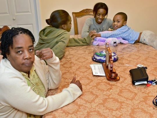 Marie Nicole Louise, left, sits at the kitchen table