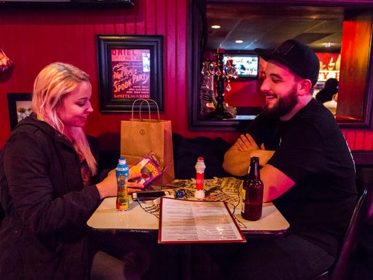 Brianna Gordon (left) checks out her prize as she sites with Ryan Manuel during an adult bingo game at the Oddity Bar on Wednesday night.