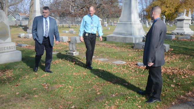 Detectives Jim Tuyls, from left, Randy Reinstein and Nick Woolman searched Oak Hill Cemetery Tuesday for any possible evidence dropped by the suspect after a shooting Sunday on Post Avenue.