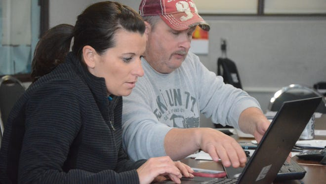 Erin Deloof, a parole and probation agent, and Detective Jeff Coons work on computers searching for woman working as prostitutes.