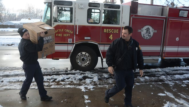 Firefighter Gary Metheny, left and Lt. JD Ramey deliver food  Sunday for a Thanksgiving meal.