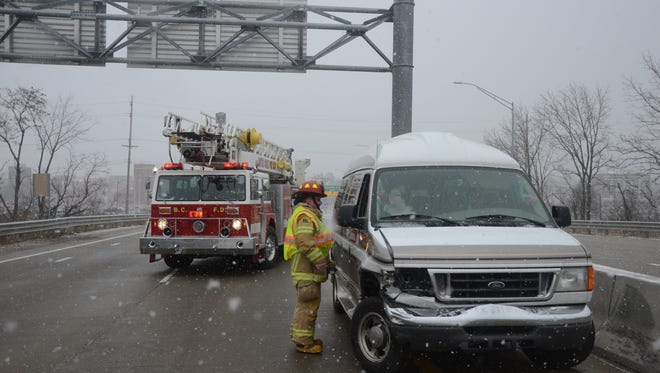 Battle Creek firefighters check the people in a van which crashed on southbound M-66.