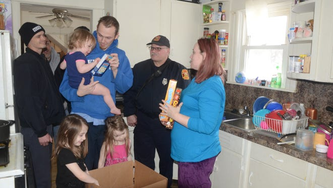 Jacen Hughes, center, holding Riley, 20 months, and Rebecca Hughes along with two more daughters, Jaden, 6, left, and Kae-lea, 4, had Christmas dinner delivered by Battle Creek firefighters, Michael Tobin, left, and Lt. Brian Bartzen.