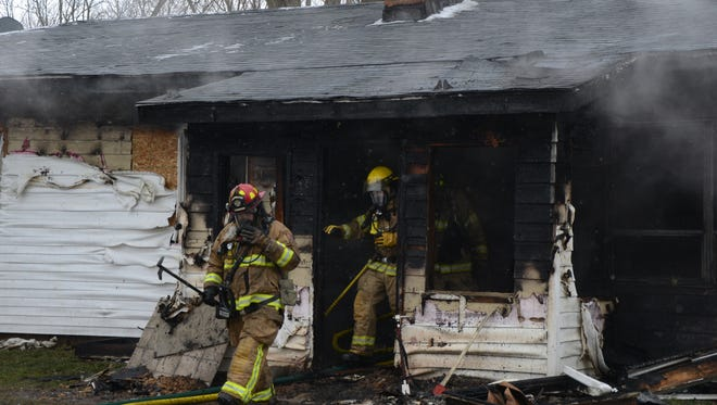 Firefighters leave the front of the house on Gardenia Street where a fire began Wednesday.