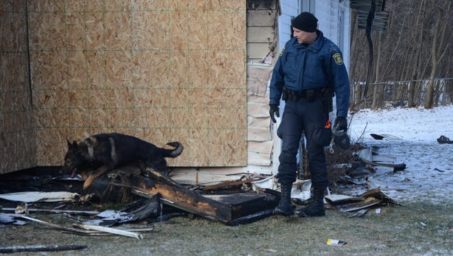 Michigan State Police Trooper Joel Service and his dog Ki search the burned home on Thursday.