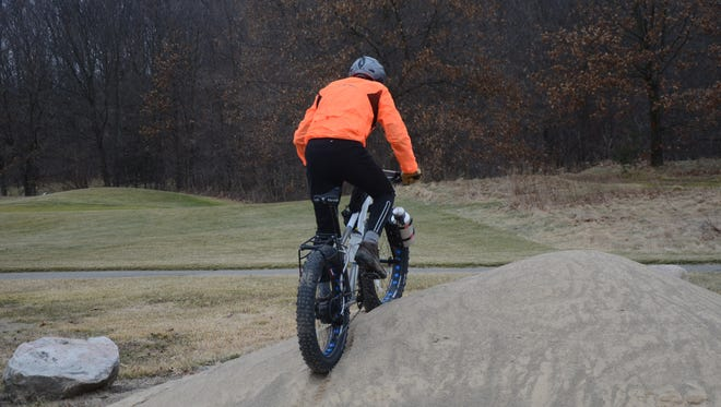 Mike Wood rides over a pile of sand on his fat bike.