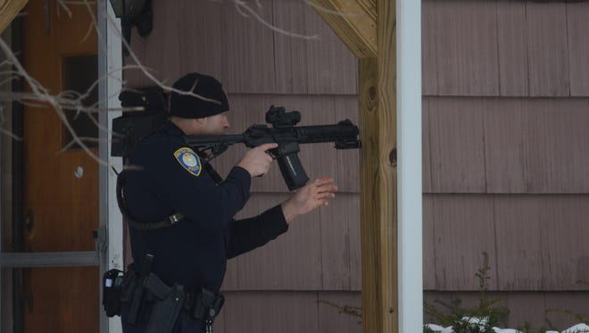 An officer takes position after a man hid in a house Saturday.