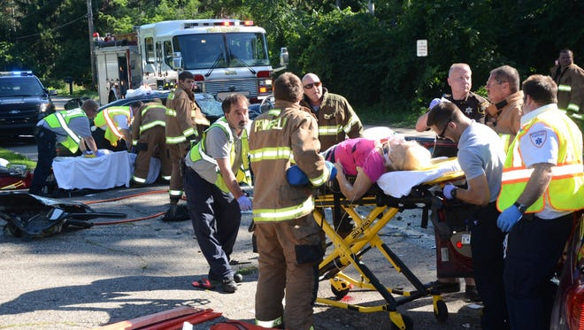 A woman from Canton, Mich. is taken to an ambulance after she was removed from her car. Rescue workers continue to extricate a passenger in the other car.