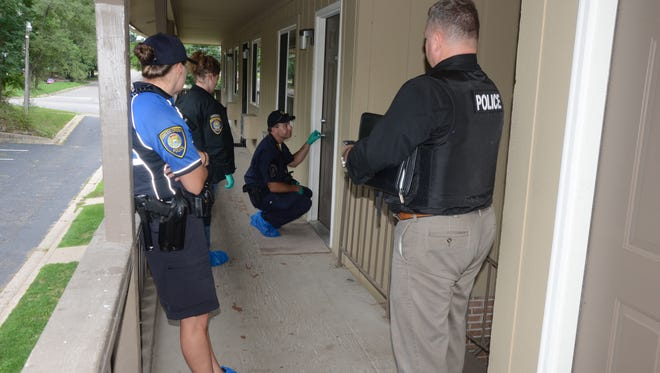 Battle Creek Detectives and crime laboratory technicians prepare to enter an apartment Monday where a woman was fatally injured.