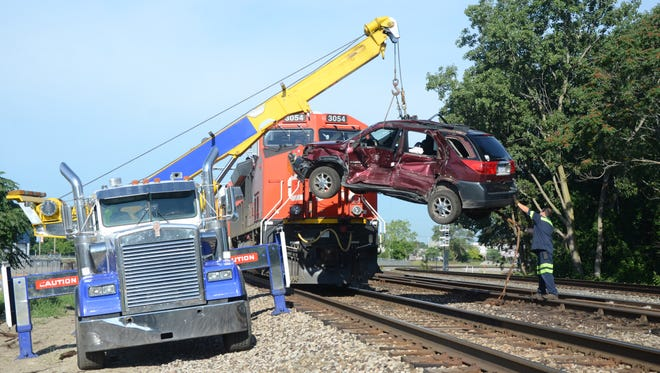 Wrecker operators used a crane to lift the car off the tracks.