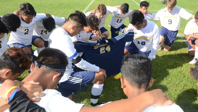 Battle Creek Central soccer players huddle in prayer before their game against Kalamazoo Home School on Monday.