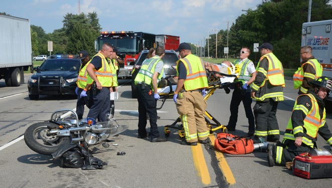 Paramedics and firefighters taken a motorcycle rider to an ambulance after a Tuesday crash.