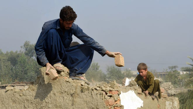 An Afghan refugee family demolishes their house before returning to Afghanistan.