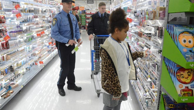 Shantina Benjamin, 8, was looking for a gift for her mother with help from Cadet Ryan Ferguson, left, and Explorer Esteban Gancer of the Battle Creek Police Department.