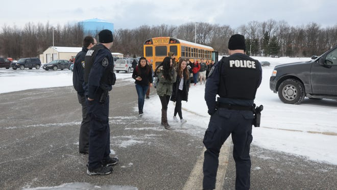 Battle Creek officers watch as students from Lakeview leave their bus after a Feb. 3 school evacuation.