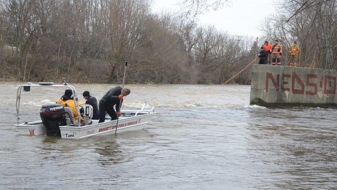 Searchers in a boat from Emmett Township look for the missing car near the convergence of the Kalamazoo and Battle Creek rivers west of Washington Street.