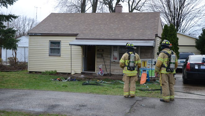 Battle Creek firefighters outside the home damaged by a Thursday explosion.