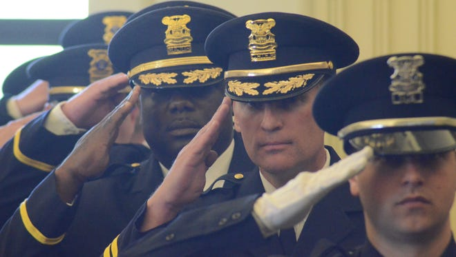 Officer Jed Reames, front to back, Chief Jim Blocker and Major Austin Simons salute the flag during the ceremony.