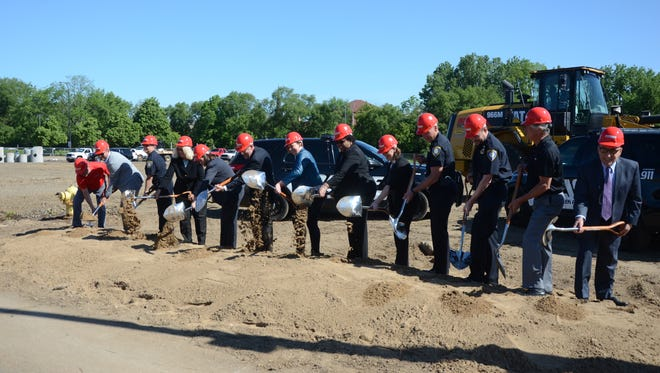 Dignitaries turn the soil at a groundbreaking for the new Battle Creek police station.