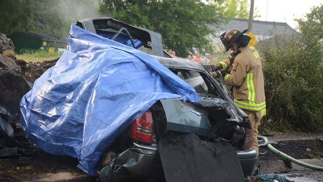 Firefighters continue to put water on the remains of the burned car.