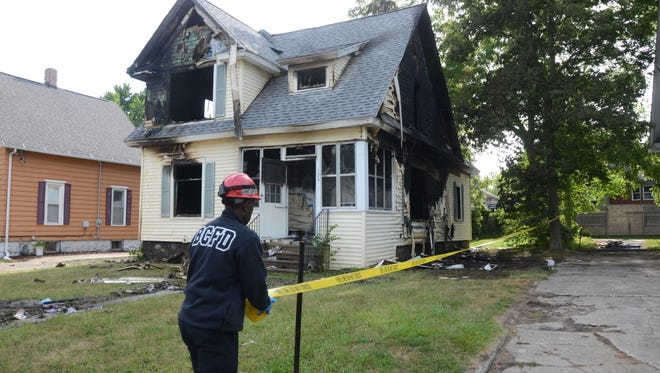 Battle Creek Fire Marshal Quincy Jones tapes the area around a burned house on Caine Street Wednesday, June 28, 2017.
