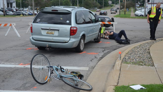 Battle Creek police photograph the undercarriage of a van after a bicyclist was struck and dragged under the vehicle Thursday afternoon.