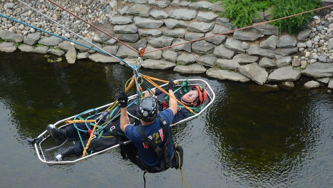 Captain Dan Wolfe is in the basket and Firefighter Kurt Hoeksema is helping guide the rescue basket to the ground near the Battle Creek River Thursday, Aug. 3, 2017.