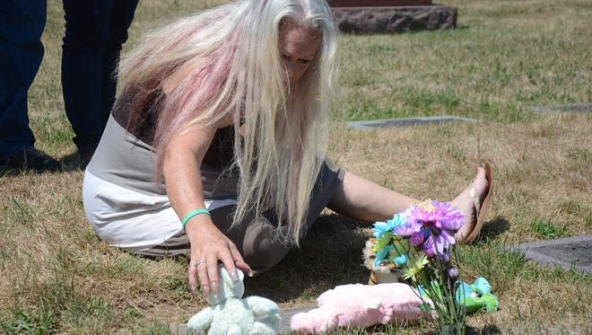 Robin Buonodono sits Saturday at the grave of her daughter, Nicole VanNoty in Memorial Park Cemetery in Battle Creek.