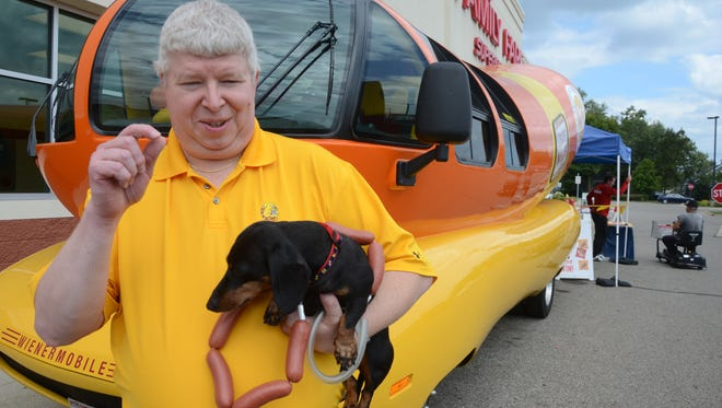 With his dachshund, Gracie, on a hot dog leash, Mike Alverson visited the Wienermobile Wednesday.