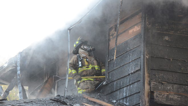 A Battle Creek firefighter checks outside the badly burned second floor on Surby Avenue Friday, Sept. 15, 2017.
