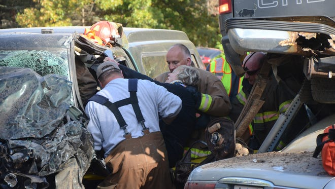 Firefighters free D'Lynn Smith of Charlotte from her truck after a three-vehicle crash in Pennfield Township on Oct. 21. Smith, a preschool teacher, sustained several broken bones.
