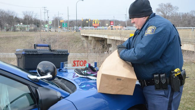 Michigan State Police Trooper Jason Mead collects some evidence at the scene along I-94 and Capital Avenue where the body of a woman was found Wednesday.