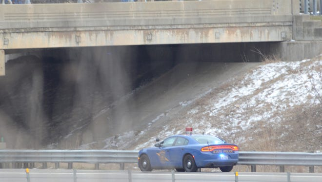 A Michigan State Police trooper is parked along the eastbound shoulder of I-94 at Capital Avenue where the body of a woman was found Wednesday afternoon.