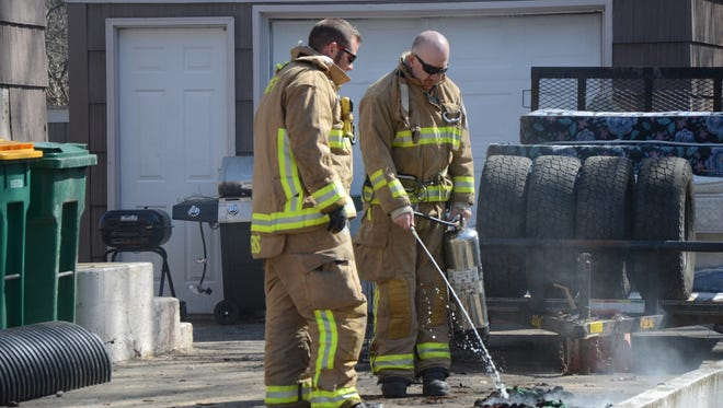 Firefighters extinguish some burning material brought from a homeat 138 Lacey Ave. in Battle Creek on Thursday, April 5, 2018.