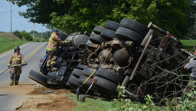 Pennfield Township firefighters check leaks after a semi rolled onto its side avoiding another vehicle.
