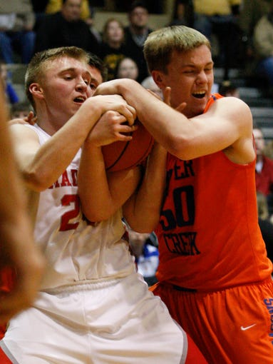 Silver Creek's Christian Reed, #50, right, wrestles Madison's Carson Wattenbarger, #24, for possession during their game at the North Harrison High School. Mar. 5, 2014