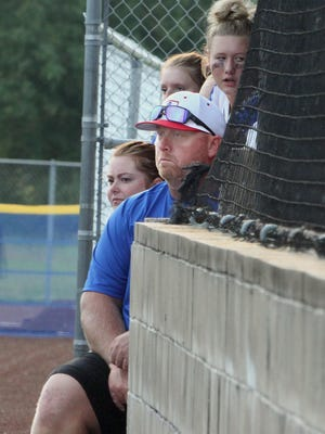 Moberly varsity girls head softball coach Ryan Taylor and his assistant coach Ashley Crutchfield sit  at the edge of the dugout entrance as they observe action taking place during a home game played at General Omar Bradley Field. The Lady Spartans suffered a 16-2 home loss Wednesday to Hallsville.