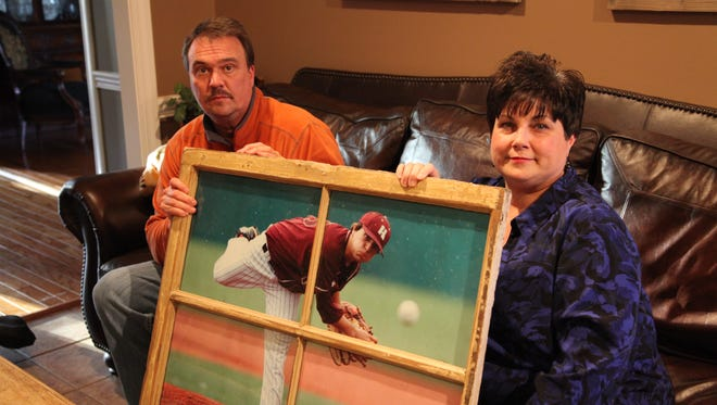 Mike and Liz Wroten are shown at their home holding a photo of their son, Chase, pitching for Hinds Community College.  Chase died April 15, 2011, two days after suffering a stroke.