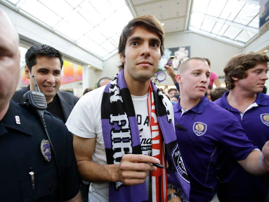 Brazilian soccer star Kaka, center, surrounded by security and police officers, makes his way through a crowd of fans at Orlando International Airport, Monday, June 30, 2014, in Orlando, Fla. Kaka is the first designated player to sign with the Orlando City Soccer Club and the team will begin play in Major League Soccer in 2015. (AP Photo/John Raoux)